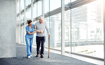 Nurse walks with a patient using a cane